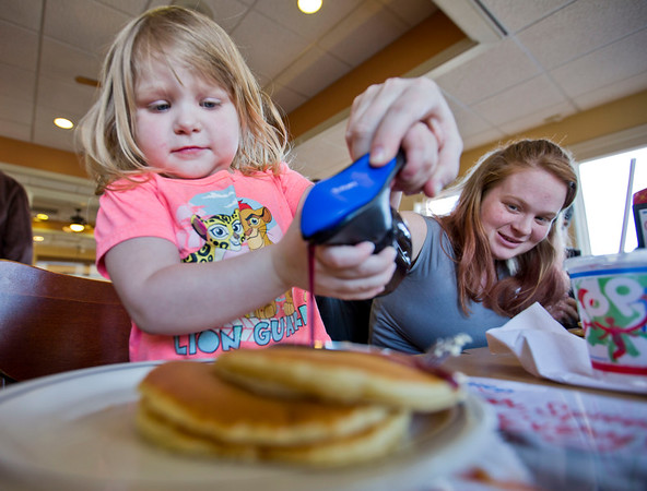 JAY YOUNG | THE GOSHEN NEWS<br /> Three-year-old Peyton Reployle gets a little help from her mother Autumn as they pour syrup on a short stack of pancakes at IHOP on Tuesday afternoon. Tuesday was National Pancake Day at IHOP. The restaurant was offering a free short stack of pancakes in exchange to a donation to one of three charities. The charities are The Children's Miracle Network Hospitals, Shrines Hospitals for children and the Leukemia and Lymphoma Society.