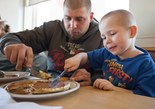 JAY YOUNG | THE GOSHEN NEWS<br /> Four-year-old Logan Reployle gets some help from his dad, Kyle Najacht as they cut into a stack of pancakes at IHOP on Tuesday afternoon. Tuesday was National Pancake Day at IHOP. The restaurant was offering a free short stack of pancakes in exchange to a donation to one of three charities. The charities are The Children's Miracle Network Hospitals, Shrines Hospitals for children and the Leukemia and Lymphoma Society.