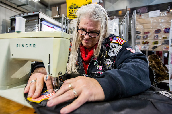 JAY YOUNG | THE GOSHEN NEWS<br /> Bonnie Wann, of Bern, sews an American flag patch onto a leather riding jacket at the Abate of Indiana's 32nd annual Region One Elkhart County Swap Meet on Sunday morning at the Northern Indiana Event Center in Elkhart.