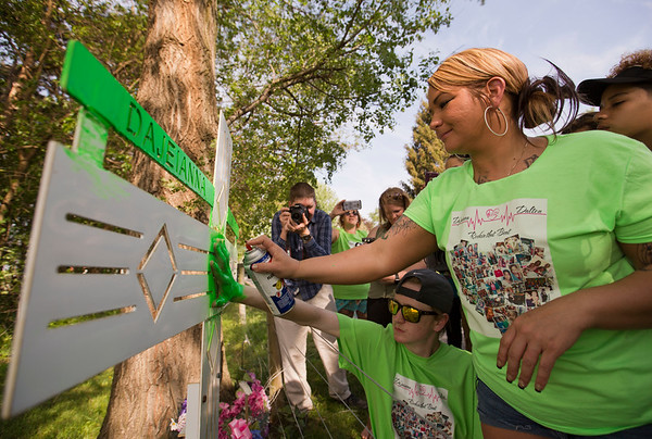 JAY YOUNG   THE GOSHEN NEWS<br /> Valerie Matthews uses green spray paint to outline Dalton Igoe's hand on the memorial of her daughter, Da'Jeianna Tuesday afternoon in Elkhart. In 2012, Da'jeianna was killed after being struck by a truck on C.R. 108 while she walked home school. As a result of the accident, Dalton, who has suffered from heart problems since birth, received Da'jeianna's heart.
