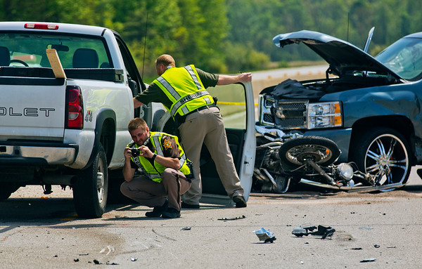JAY YOUNG | THE GOSHEN NEWS<br /> Officers from the Elkhart County Sheriff Department work the scene of a fatality accident involving multiple vehicles and a motorcycle Tuesday afternoon at the intersections of C.R. 17 and C.R. 18.