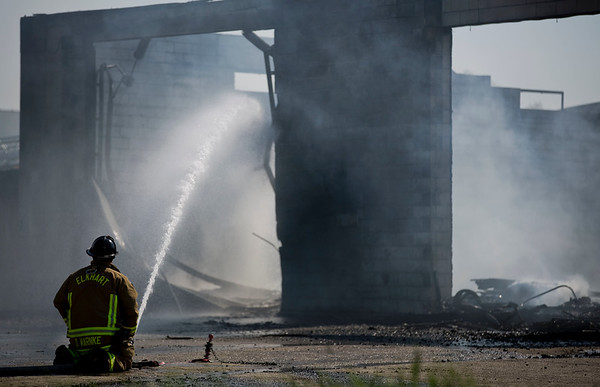 JAY YOUNG | THE GOSHEN NEWS<br /> A firefighter with the Elkhart Fire Department mans a hose as he extinguishes hot spots at a structure fire in the 2800 block of Oakland Ave. in Elkhart Sunday afternoon. The building, owned by Forest River, Inc., was vacant and empty at the time of the fire.