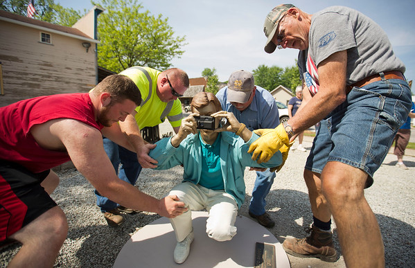 JAY YOUNG | THE GOSHEN NEWS<br /> Zach BeMiller, left, of Wakarusa, and Nick Kulp, of Wakarusa, along with others unload a sculpture by Seward Johnson Tuesday morning next to the quilt garden plot near downtown.