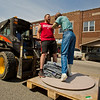 JAY YOUNG | THE GOSHEN NEWS<br /> Finding a different way to travel through downtown Wakarusa Tuesday morning, Zach BeMiller, of Wakarusa gets a lift from a forklift driven by Terry Flickinger, of Wakarusa, while holding onto a sculpture by Seward Johnson that is being installed in front of Cook's Pizza.