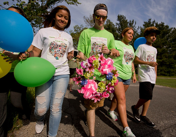 JAY YOUNG | THE GOSHEN NEWS<br /> Dalton Igoe, center, is flanked by Dahjahnay Ware on the left and Valerie Matthews on the right as they walk down C.R. 108 in Elkhart Tuesday afternoon. In 2012, Matthew's daughter and Ware's sister, Da'jeianna Ware, was struck and killed by a truck while walking home from school along the road. Igoe, who suffered heart problems since birth, received Da'jeianna's heart as a result of the accident. This was his first time visiting Elkhart and the site of the accident.
