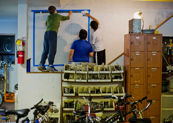 """JAY YOUNG   THE GOSHEN NEWS<br /> Goshen Middle School sixth-grade students, from left, Joshua Carpenter, Logan Lagunas and Tyrell Bowen paint a cycling mural after laying out a square grid on wall inside Chain Reaction Bicycle Project, 510 East Washington Street, Tuesday afternoon. The students, who are part of the New Tech program, involved in a project called The Goshen Renaissance and were painting murals at businesses and organizations around the city. """"The whole project is about connecting to the European Renaissance,"""" Jared Leaman, a social students teacher at the school, said. """"We connected it to the European Renaissance to find out what kind of arts and cultural aspects are happening in Goshen right."""" Various disciplines are involved in the project. In math, students were learning about topics such as size and scale. Students in English classes wrote proposals to send to the businesses involved. In social studies, students learned all about the European Renaissance and art. About 125 students are involved in the New Tech program. Each of them created an original design for a mural and about 20 were selected to be painted."""