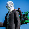 "JAY YOUNG | THE GOSHEN NEWS<br /> Adam Garey stands on a cherry picker to reach the top of the 25 foot tall monumental Seward Johnson sculpture ""God Bless America"" as he unfastens a belt used to hoist the 3,000 pound statue upright Monday morning at Central Park in Elkhart. The sculpture, inspired by Grant Wood's famous painting, ""American Gothic,"" is part of a Seward Johnson exhibition featuring 56 life-sized sculptures and one monumental sculpture that are installed throughout Elkhart County in conjunction with the 10th anniversary of the Quilt Garden."