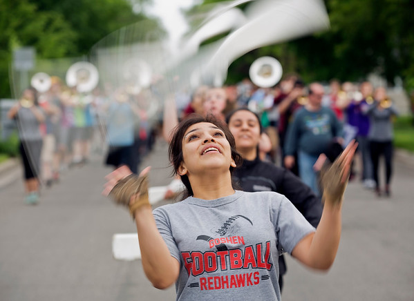 JAY YOUNG | THE GOSHEN NEWS<br /> Goshen High School junior Sandra Contreras twirls a wooden practice rifle as she and the rest of the color guard lead the marching band along East Reynolds Street as they practice Thursday evening for their upcoming performance in the Indianapolis 500 parade.
