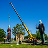 "JAY YOUNG | THE GOSHEN NEWS<br /> After bolting down the farmer, workers with the Seward Johnson Atelier use a crane to maneuver the farmer's daughter into position on the sculpture base Monday morning during an installation of the 25 foot tall monumental Seward Johnson sculpture ""God Bless America"" at Central Park in Elkhart. The sculpture, inspired by Grant Wood's famous painting, ""American Gothic,"" is part of a Seward Johnson exhibition featuring 56 life-sized sculptures and one monumental sculpture that are installed throughout Elkhart County in conjunction with the 10th anniversary of the Quilt Garden."
