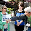 SHEILA SELMAN | THE GOSHEN NEWS<br /> Tour guide Jerry Kindy, right, points to a building in a photo held by Kim Clarke of Middlebury. Looking on is Hannah Walsh of Middlebury, who took the run-through tour Wednesday.