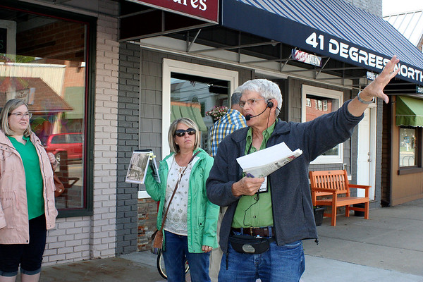 "SHEILA SELMAN | THE GOSHEN NEWS<br /> Middlebury walking tour guide Jerry Kindy, right, leads a group around the downtown explaining the history of building and giving some colorful historical stories. The tour was titled ""Gangsters, Saloons and Buggies on Roofs."""