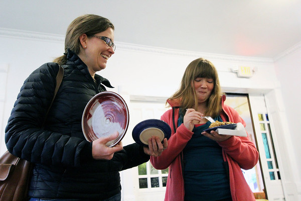 GEOFF LESAR | THE GOSHEN NEWS<br /> <br /> Betsy McCanse, Goshen, and her daughter Zoë Sherbit, St. Joseph, Michigan, overlook a table of ceramic plates during Goshen Youth Arts' Pie and Plate fundraiser Saturday evening.
