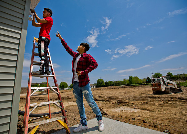 JAY YOUNG | THE GOSHEN NEWS<br /> Goshen High senior Cornelio Rangel points to the light on the back of a voltmeter that junior Christyan Torres uses to check the voltage of a light fixture wire during their Building Trades class Wednesday afternoon. The class is working on a home at 1530 Sandpiper Lane in Goshen.