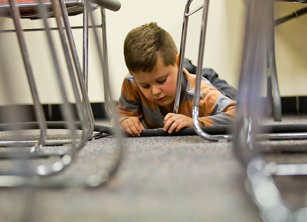 JAY YOUNG | THE GOSHEN NEWS<br /> Six-year-old Vincent Castillo-Miller, of Goshen, threads pipe insulation underneath metal chair legs as he puts together a marble rollercoaster during Family Science Night at the Goshen Public Library Thursday evening. On the second Thursday of each month, the library hosts a S.T.E.A.M. inspired Family Science Night with the goal of teaching children basic science topics while having fun. This month's topic was physics. Participants learned about potential energy, kinetic energy and momentum by building marble rollercoasters out of pipe insulation and masking tape.