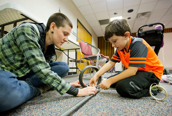 JAY YOUNG | THE GOSHEN NEWS<br /> Seven-year-old Aiden De La Fuente gets some help from his mom, Christine, as they create a loop in their rollercoaster track during Family Science Night at the Goshen Public Library Thursday evening. On the second Thursday of each month, the library hosts a S.T.E.A.M. inspired Family Science Night with the goal of teaching children basic science topics while having fun. This month's topic was physics. Participants learned about potential energy, kinetic energy and momentum by building marble rollercoasters out of pipe insulation and masking tape.