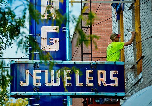 JAY YOUNG | THE GOSHEN NEWS<br /> Perched high above, Bill Lambie, of Lambie's Painting in Osceola, paints a second floor window sill above Sorg Jewelers on Main Street in downtown Goshen Thursday afternoon.