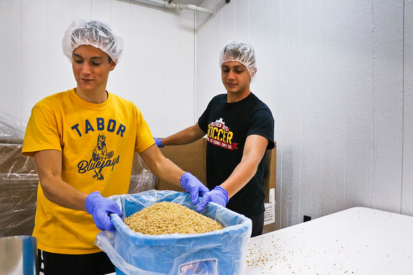 LEANDRA BEABOUT | THE GOSHEN NEWS<br /> High school seniors Jeremiah Hostetler and Michael Bontrager transport a container of soy.