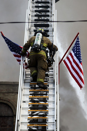JAY YOUNG | THE GOSHEN NEWS<br /> A firefighter climbs a ladder truck as he works to put out a large fire in downtown LaGrange Tuesday afternoon.