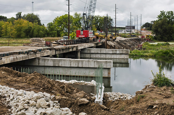 JAY YOUNG | THE GOSHEN NEWS<br /> Despite heavy cloud cover and intermittent rain, work continues Wednesday afternoon on the Kercher Road bridge that spans the Elkhart River.