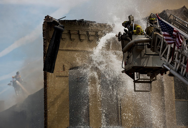 JAY YOUNG | THE GOSHEN NEWS<br /> A firefighter adjusts the pressure to a hose while multiple aerial trucks battle a large fire in downtown LaGrange Tuesday afternoon.