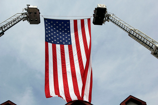 ADAM RANDALL | THE GOSHEN NEWS<br /> Fire ladders hoist an American flag Monday at Concord Fire Station No. 1.