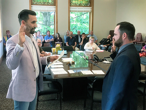 JOHN KLINE | THE GOSHEN NEWS<br /> Goshen Mayor Jeremy Stutsman, left, promotes Jared A. Ellison to the rank of probationary patrol officer with the Goshen Police Department during the Goshen Board of Public Works and Safety meeting Monday afternoon.