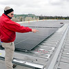 BEN MIKESELL | THE GOSHEN NEWS<br /> Glenn Gilbert, director of facilities at Goshen College, examines the solar panels being installed on the roof of the Rec-Fitness Center on campus Wednesdsay. Gilbert said there will be 924 total panels installed by the end of the week.