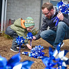BEN MIKESELL | THE GOSHEN NEWS<br /> Drake Allen, 2, plants pinwheels outside of Child & Parent Services (CAPS) in Elkhart Monday with the help of his dad Justin, a CAPS employee. The duo from Elkhart were among many volunteers and CAPS employees who planted pinwheels outside the facility on Hively Avenue to honor National Child Abuse Prevention Month.