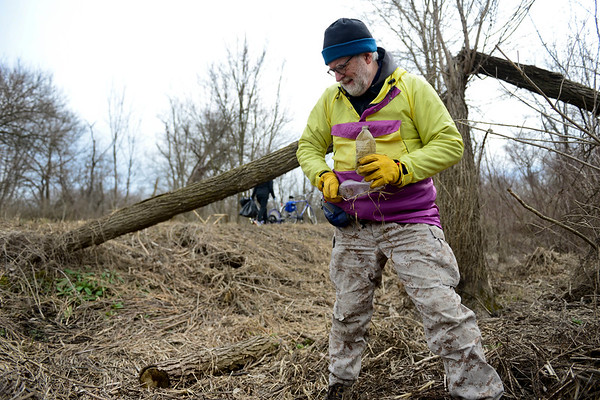 BEN MIKESELL | THE GOSHEN NEWS<br /> Tyler Klassen, shop manager at Chain Reaction Bicycle Project, crushes a plastic bottle while cleaning up the Pumpkinvine Trail Thursday near Abshire Park. Klassen organized the clean up effort as a way to give back to the Goshen Parks Department.
