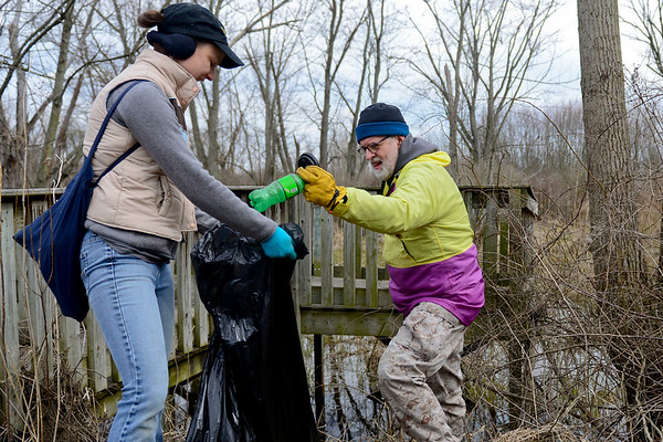 BEN MIKESELL   THE GOSHEN NEWS<br /> Tyler Klassen, shop manager at Chain Reaction Bicycle Project, cleans up the Pumpkinvine Trail Thursday with the help of board member Andrea Milne near Abshire Park in Goshen. Klassen organized the clean up effort as a way to give back to the Goshen Parks Department, in preparation for the national Opening Day for Trails on April 7.