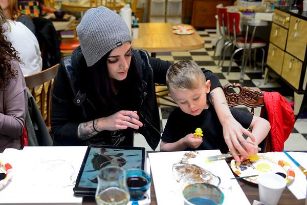 BEN MIKESELL | THE GOSHEN NEWS<br /> Andrea Sandusky and her son Landon, 4, of Goshen paint pictures of their pit bull Dahlia during Pet Portrait Day Thursday at Home Again Consignment.