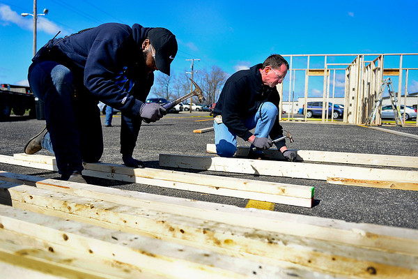 "BEN MIKESELL | THE GOSHEN NEWS<br /> Lippert Components employees Christian Roberson, left, and Todd Bontrager, right, work on door frames for a Habitat for Humanity home Thursday morning in the parking lot of Lippert Components Plant 85 in Goshen. The home is being made for a grandmother, mother and her three kids. Lippert Components helped build the framework for the house, and it will be transported in sections to its location in Bristol. ""I'm a little out of my element,"" Roberson said, ""but I like helping and being a part of this."""
