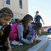 GEOFF LESAR | THE GOSHEN NEWS<br /> <br /> Jaylen Yoder, left, Emily Diaz, center and Aaliyah Lucas, members of the Boys & Girls Club of Goshen, push their pinwheels into the club's lawn Friday afternoon following an address by representatives of CAPS, Bashor Home, among others. Goshen Mayor Jeremy Stutsman declared April Child Abuse Prevention Month for the city of Goshen.