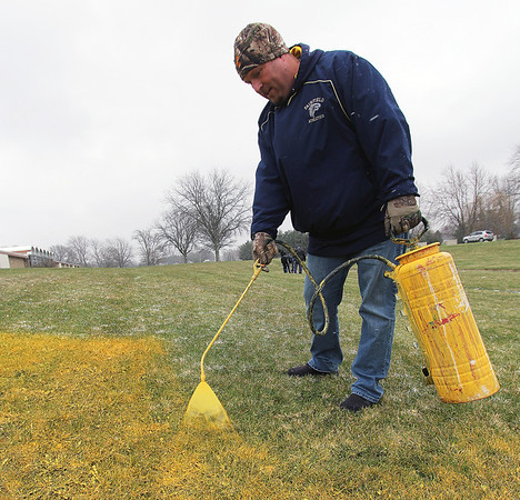 Roger Schneider | The Goshen News<br /> Fairfield Sr.-Jr. High Assistant Principal Nick Jones sprays yellow paint on grass outside the school Monday to create the background of artwork that will represent unity at the school. Students and staff are expected to finish the artwork today as a way of presenting an anti-bullying message ahead of the April 20 anniversary of the Columbine High School mass shooting that occurred in 1999.