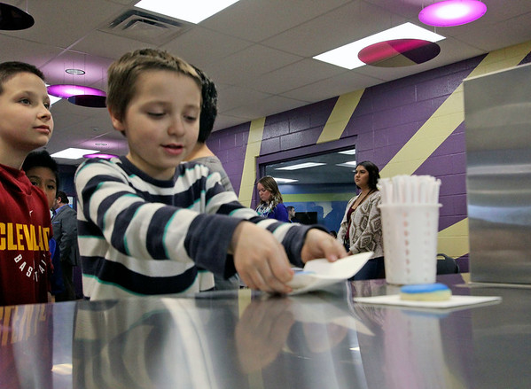 GEOFF LESAR | THE GOSHEN NEWS<br /> <br /> Kaleb McGlothen, a Boys & Girls Club of Goshen member, reaches for his cookie Friday afternoon prior to an address by representatives of CAPS and  Bashor Home, as well as Goshen Mayor Jeremy Stutsman.