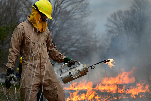 BEN MIKESELL   THE GOSHEN NEWS<br /> Goshen College sophomore Jesse Amstutz uses a drip torch to set a prairie on fire April 13 for his environmental science class at Goshen College. The exercise is part of a long-term research project for the Roots of the Enviromental Crisis class taught by professor Ryan Sensenig.