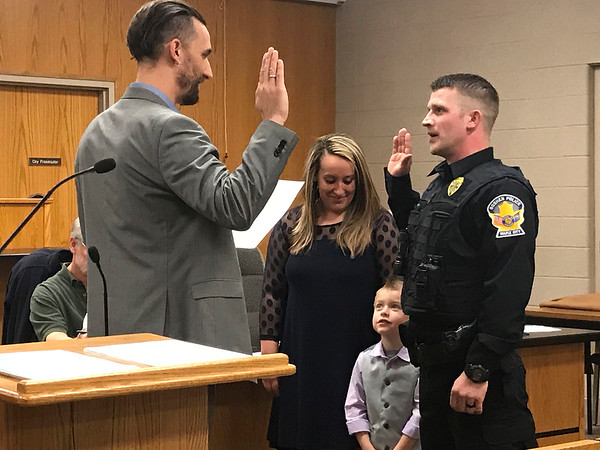 JOHN KLINE | THE GOSHEN NEWS<br /> Goshen Mayor Jeremy Stutsman, left, swears in Aaron D. Johnson, right, as a new probationary patrol officer with the Goshen Police Department during Monday's Board of Public Works and Safety meeting.