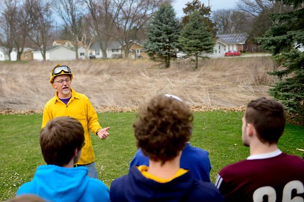 BEN MIKESELL   THE GOSHEN NEWS<br /> Goshen College professor Ryan Sensenig briefs his students on how to properly burn the prairie behind him April 13 on Goshen College's campus.