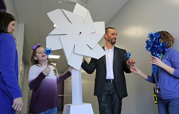 GEOFF LESAR   THE GOSHEN NEWS<br /> <br /> Sophia Mangona and Goshen Mayor Jeremy Stutsman carry a giant pinwheel through the halls of the Boys & Girls Club of Goshen as club employee Kimi Ehret hands off a smaller pinwheel and employee Natalie Yoder looks on Friday afternoon. Stutsman addressed club members earlier, declaring April Child Abuse Prevention Month for the city of Goshen.