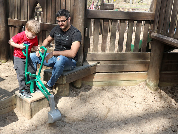SHEILA SELMAN   THE GOSHEN NEWS<br /> Noah Stanley, 3, Goshen, scoops sand while his uncle, Shawn Wilson, watches Monday afternoon at Tommy's Kids Castle at Shanklin Park in Goshen.