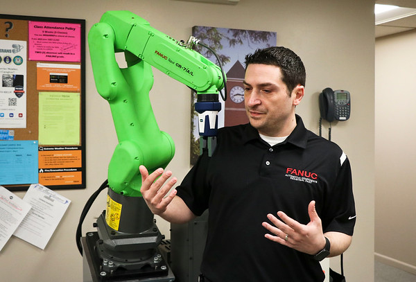LEANDRA BEABOUT | THE GOSHEN NEWS<br /> Larry Marino demonstrates how the FANUC robot stops moving when it hits his shoulder, which is a safety feature of the machine.