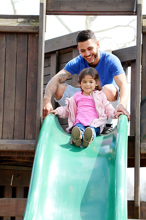 SHEILA SELMAN | THE GOSHEN NEWS<br /> Camila Rivera, 2, prepares to slide down the tall slide as Motley Rivera, Goshen, looks on Monday afternoon at Tommy's Kids Castle at Shanklin Park in Goshen.