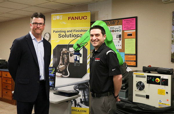 LEANDRA BEABOUT | THE GOSHEN NEWS<br /> Dave Wagenhauser and Larry Marino of FANUC Robotics stand next to one of the company's robots.