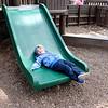 SHEILA SELMAN | THE GOSHEN NEWS<br /> After multiple slides, Rhett Byng, 3, Goshen, decides to take a momentary break on the slide at Tommy's Kids Castle at Shanklin Park in Goshen Monday afternoon.