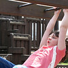 SHEILA SELMAN | THE GOSHEN NEWS<br /> Saige Kramer, 6, Wakarusa,  puts some oomph in her swing as she makes her way across the monkey bars at Tommy's Kids Castle at Shanklin Park in Goshen Monday afternoon.