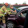 BEN MIKESELL | THE GOSHEN NEWS<br /> Topeka fireman Brian Miller helps sophomore Taylor Davis into position, who is pretending to be dead in a mock crash exercise Friday afternoon at Westview Jr.- Sr. High School. Davis, a theater student at Westview, volunteered with 3 other classmates to work with Students Against Destructive Decisions (SADD) to show the dangers of drinking and driving.