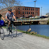 BEN MIKESELL | THE GOSHEN NEWS<br /> A pair of bicyclists ride past geese and goslings along the Goshen Mill Race Trail Tuesday in Goshen. Temperatures rose to more than 80 degrees throughout the day.