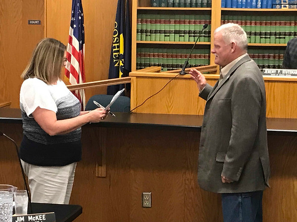 JOHN KLINE   THE GOSHEN NEWS<br /> Angie McKee, clerk-treasurer for the city, left, swears in Doug Nisley as the newest member of the Goshen City Council during the council's meeting Tuesday evening. Nisley was chosen in a special caucus Tuesday morning to fill the District 2 seat recently vacated by fellow Republican and former Goshen City Councilman Ed Ahlersmeyer.