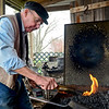BEN MIKESELL | THE GOSHEN NEWS<br /> Blacksmith Jim Rubley pulls a knife from the fire at his forge Wednesday in Shipshewana. Rubley has been crafting knives for more than 50 years, and specializes in making near replicas of a knife belonging to American explorer Daniel Boone. One of his Boone knives is was given to the Smithsonian Institution.