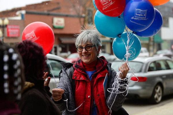 BEN MIKESELL   THE GOSHEN NEWS<br /> Bristol resident Sandy Imanse hands out balloons to people along Main Street in Goshen during April's First Friday event.